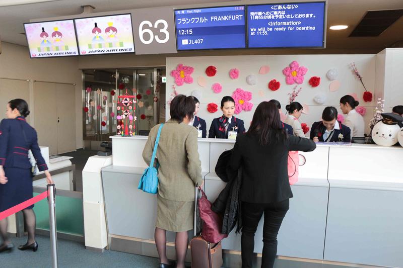 ひなあられを配り搭乗客と記念撮影。カウンター業務や搭乗客の誘導なども、すべて女性スタッフ