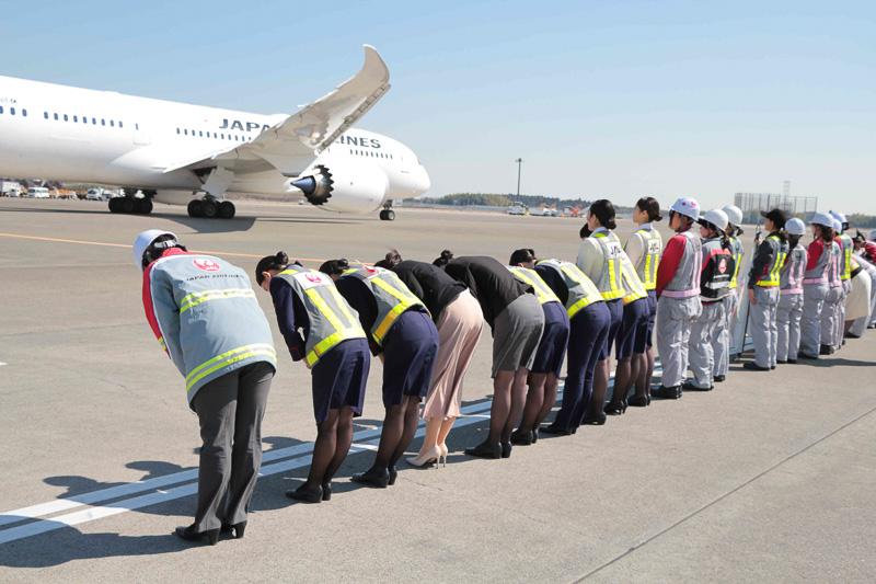 ランプでの航空機出発作業と、飛行機を見送る女性スタッフたち