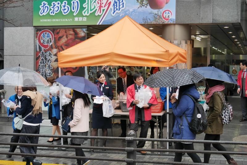 肌寒く小雨の降るあいにくの天気の中、青森県アンテナショップ「あおもり北彩館 東京店」店頭で通行人にあおもり藍フィナンシェを配布するJAL関係者