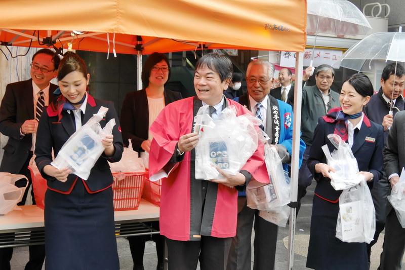 笑顔であおもり藍フィナンシェを配布する、佐藤氏や青森県出身のJAL客室乗務員ら