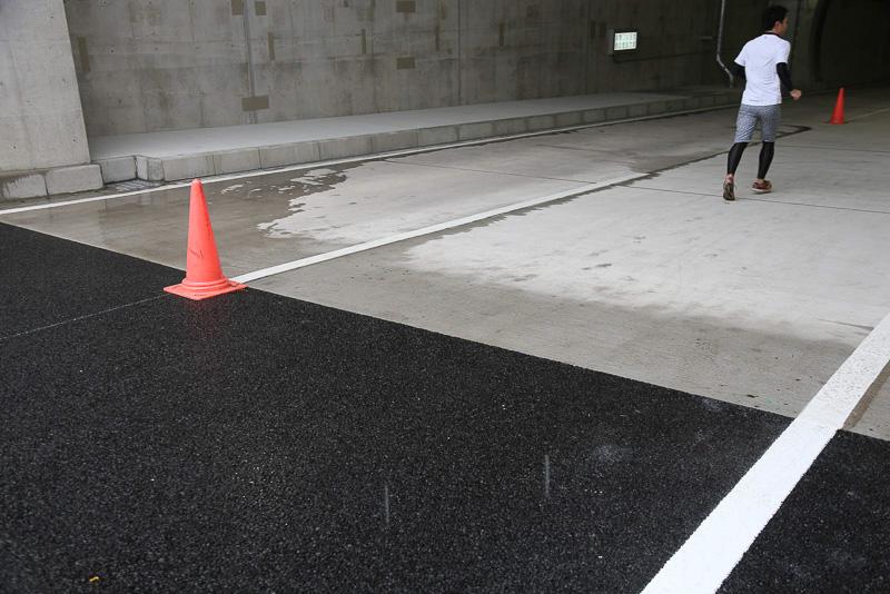 トンネル内と入り口の境目。トンネル内の舗装はコンクリート。アスファルトに比べて明るいコンクリートを使うことでトンネル内を明るく見せる効果もあるという。滑り止めのためのメッシュのような加工もされている