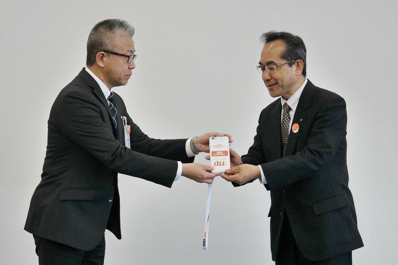 KDDI四国総支社 管理部 部長の辻美紀氏から窪氏に、多言語音声翻訳システム搭載のスマートフォンが手渡された