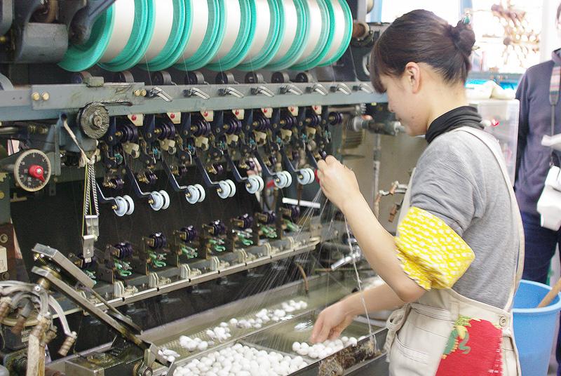 繭から糸をひっぱり、機械にかけて製糸する