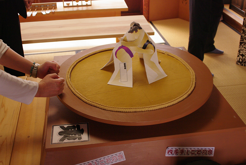 握りこぶしで土俵を叩いてその振動で力士を動かす紙相撲