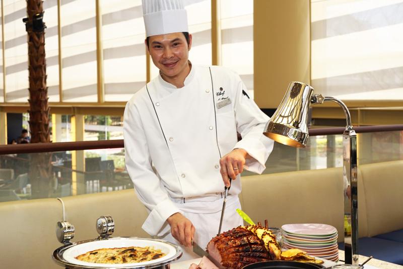 日替わりメニューの一つ。「バーボングラッセハムのレフォールクリーム添え」のハムを切り分ける「Chef X」