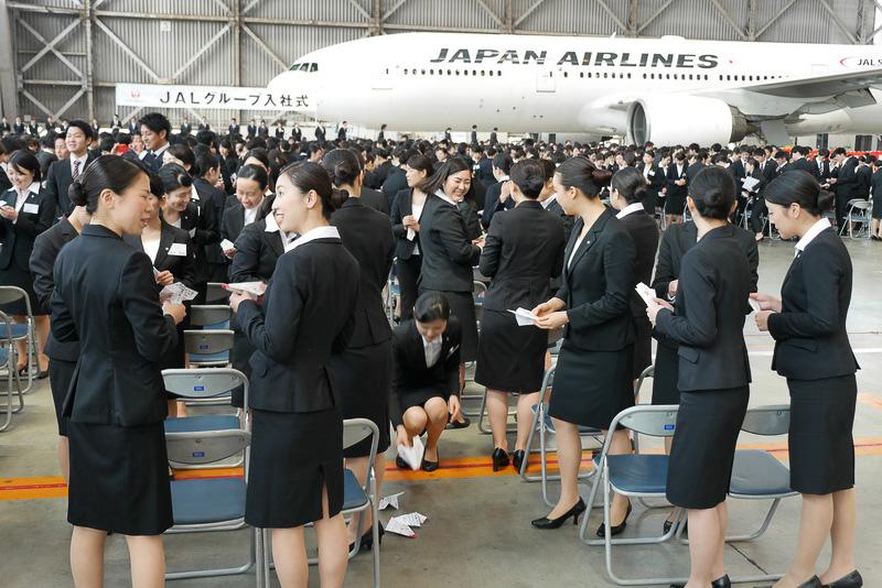 飛ばした紙飛行機は新入社員が拾い、メッセージを確認しあっていた
