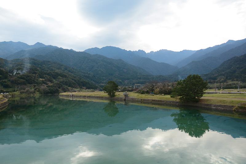 永田集落。永田橋から永田岳を望むと手前の山が十二単のように折り重なっている