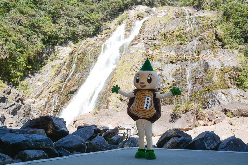大川の滝の前でポーズ。再登場の屋久島環境文化財団キャラクター「まるりん」