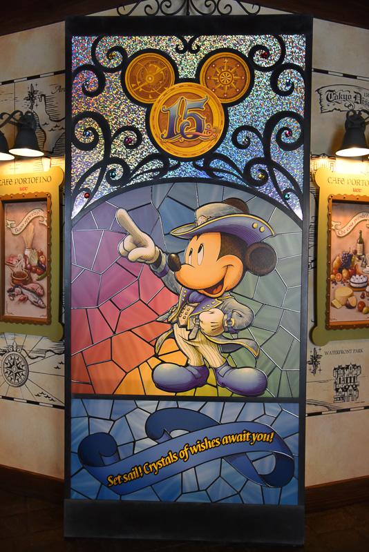 店内はステンドグラスを思わせるデコレーションが満載。15周年のコスチュームを着たミッキーマウスが描かれたデコレーションが訪れるゲストを入り口で出迎える。また、ウィンドウの装飾も同じくステンドグラフのよう
