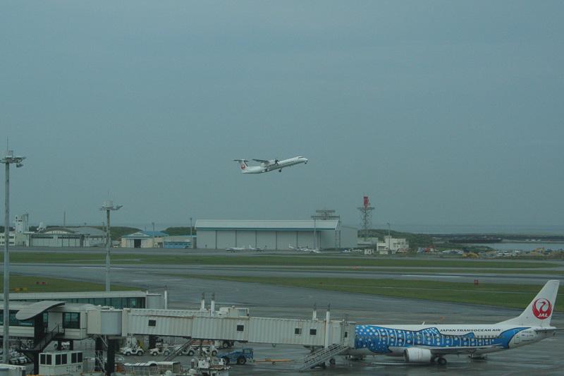 那覇空港を飛び立ったQ400CC、手前はJTA(日本トランスオーシャン航空)のジンベエジェット