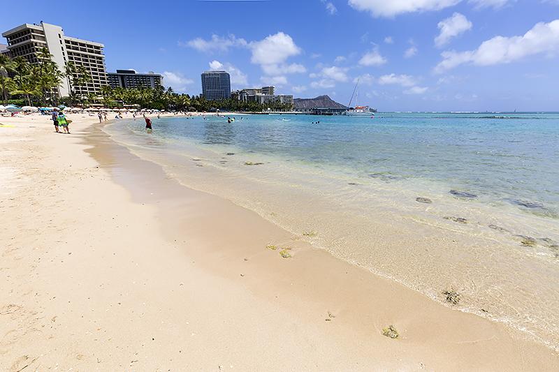 澄んだ青い海と砂浜が美しいデューク・カハナモク・ビーチ。奥にはダイヤモンド・ヘッドも望める