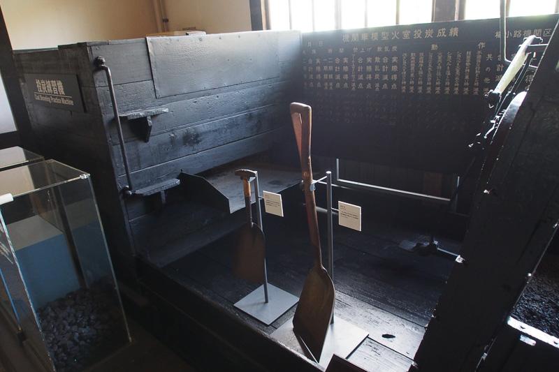 投炭練習機。石炭を火室にくべる練習をする。うしろの黒板には成績を書く欄がある