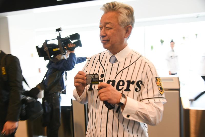 阪神タイガースのファンクラブカードを見せる佐山会長
