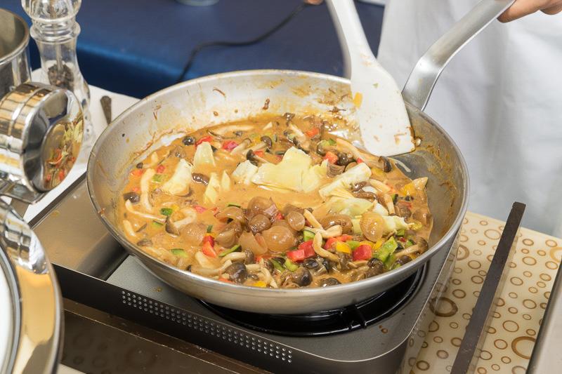 あらかじめ煮込まれたソースにアーティチョークなど野菜を入れる