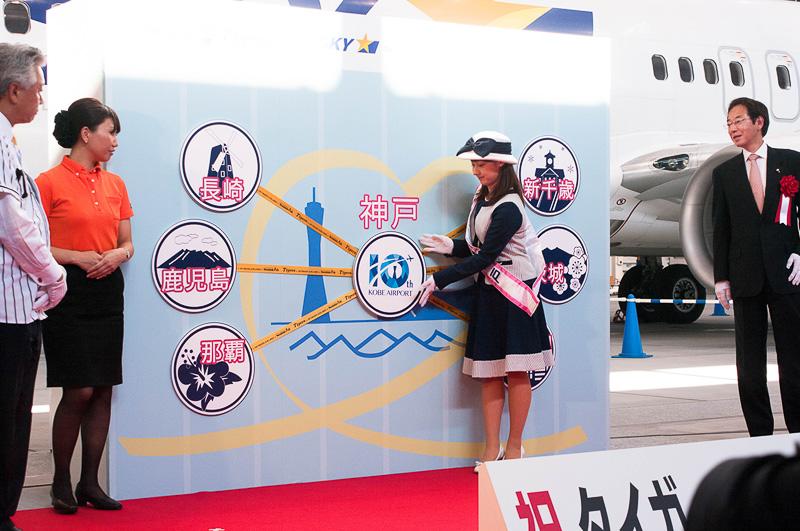 中心に神戸空港10周年のパネルを貼る親善大使スマイル神戸の額田星香さん