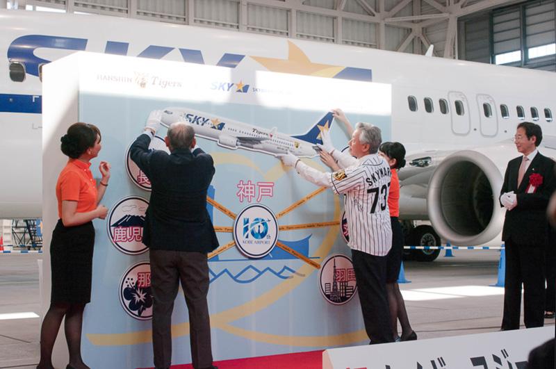 仕上げとしてタイガースジェットのパネルを設置する佐山会長と阪神OBの吉田義男氏