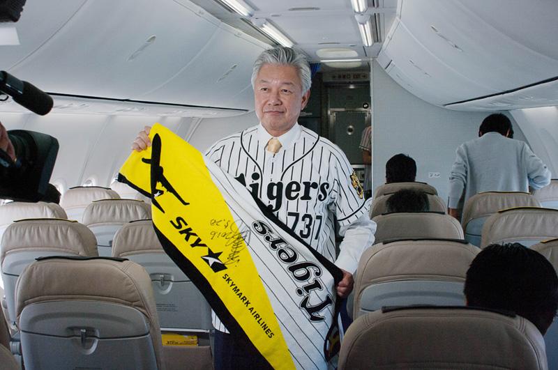 タイガースコラボタオルを広げる佐山会長。中央に書かれているのは江本孟紀氏のサイン