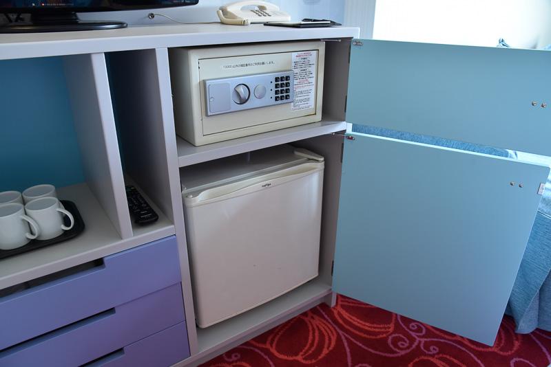 冷蔵庫は宿泊者自身が飲み物を入れるシステムのため空の状態。貴重品入れは棚の中に備え付けてある