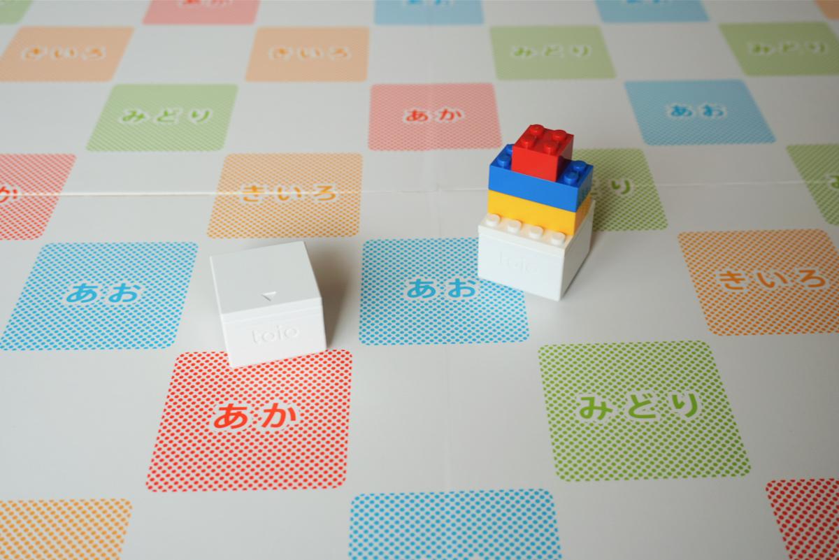2個の「toio コア キューブ」を使うプログラムもある。片方のキューブを操作すると、もう一方のキューブが鏡で映したように逆に動くプログラム。「toio」はレゴを上に組み上げられるようになっているので、自作の乗り物を作っても楽しい