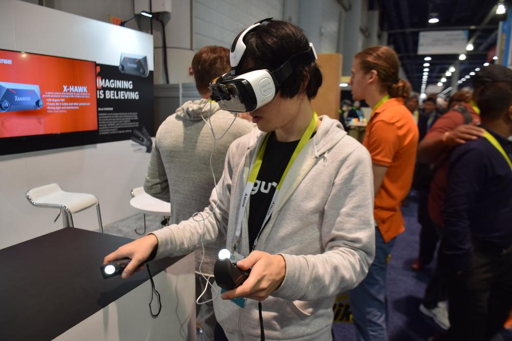 """Gear VRやモバイルVRヘッドセット向けの""""Ximmerse""""。ステレオカメラをGear VRに装着し、棒状のコントローラーと組み合わせて手の位置とプレイヤーの位置を検出する。操作性はかなり良好だ"""
